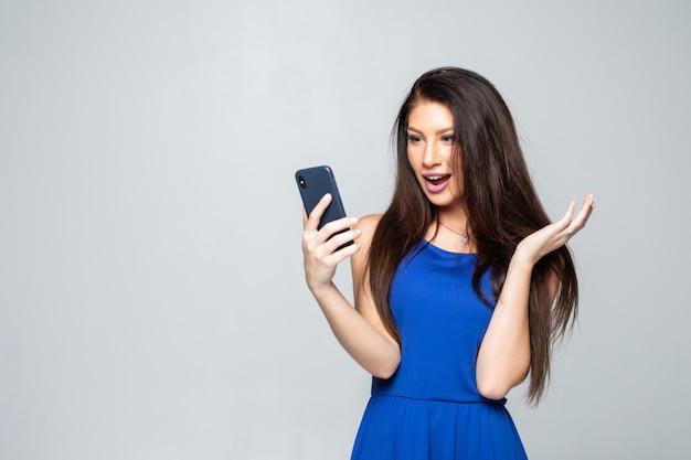 Noticias impactantes. negocios y tecnología. ciérrese encima del retrato de la mujer joven sorprendida que usa el teléfono inteligente aislado