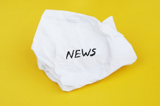 Las noticias de inscripción en papel arrugado sobre un fondo amarillo