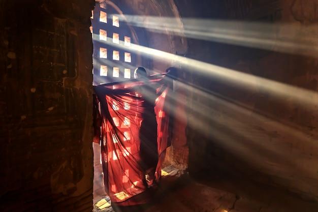 Novato budista en myanmar con túnicas en la puerta de la iglesia