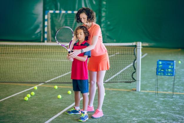 Novato. entrenador femenino en ropa brillante enseñando a un niño a jugar al tenis