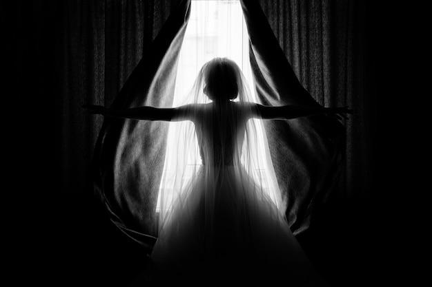 La novia abre las cortinas en la habitación del hotel.