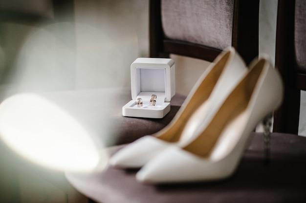 Novia accesorio de boda. zapatos blancos lacados con estilo, anillos de oro están aislados de pie sobre fondo marrón.