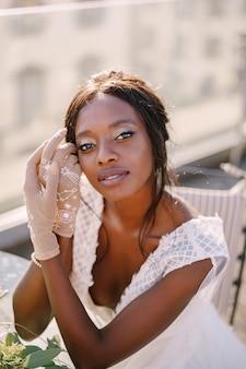 Novia afroamericana se sienta a la mesa, toca su rostro con guantes en sus manos, el ramo yace sobre la mesa