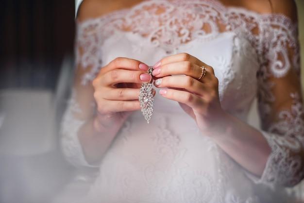 Novia con aretes de novia en manos sobre fondo de vestido blanco