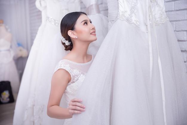 Novia asiática de la mujer joven que intenta en el vestido de boda en la boda moderna