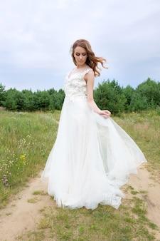 Novia atractiva joven con los ojos cerrados en el elegante vestido de novia blanco al aire libre, maquillaje y peinado