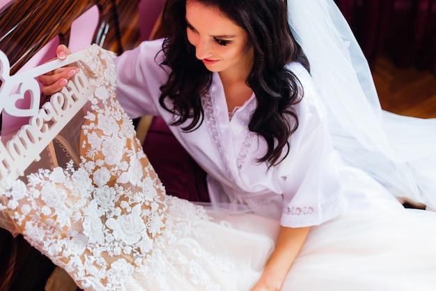 Novia en bata de baño y velo de novia sostiene una percha con una boda