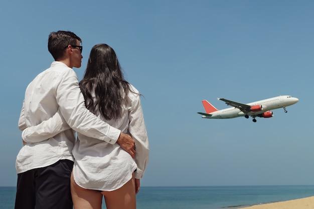 Novia en bikini y novio en camisa blanca están de pie junto al inmenso océano tranquilo y miran el avión bajo el cielo azul vista trasera
