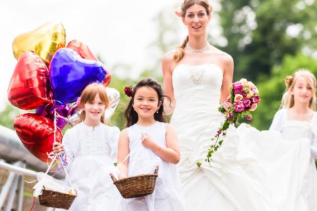 Novia de la boda en vestido con la dama de honor