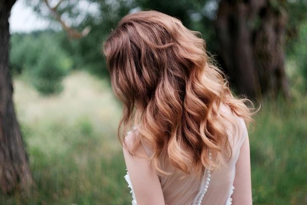 Novia bonita joven con rizos y vestido de novia blanco