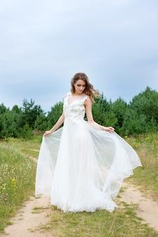 Novia bonita joven en vestido de novia blanco al aire libre, maquillaje y peinado