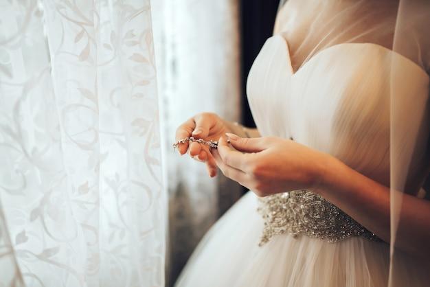 Novia bonita vestirse antes de la ceremonia de boda
