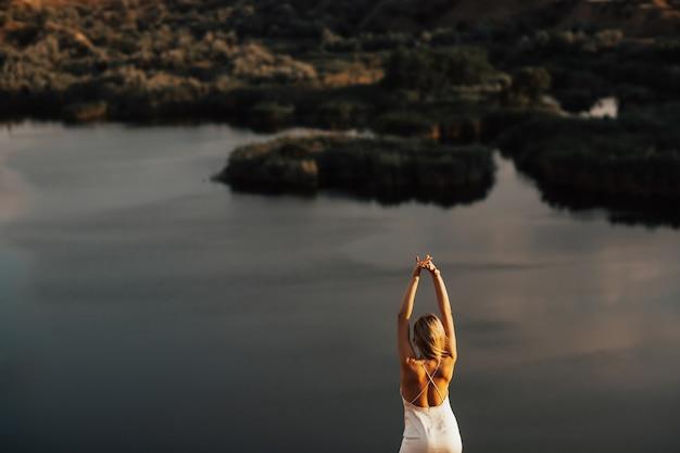 Novia de cabello rubio en vestido largo de seda blanco con las manos en alto de pie en la colina con vista al lago.