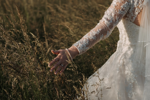 Novia caminando en un campo de trigo con un hermoso vestido de novia y una pulsera de perlas