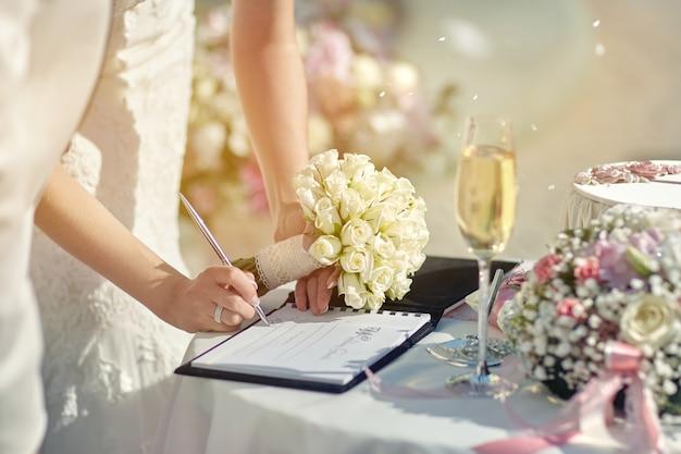 La novia de la ceromonía firma un documento.