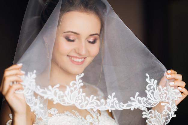 La novia se cubrió la cara con un velo de novia y mira hacia abajo.