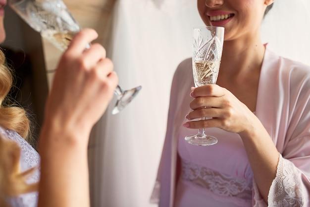 La novia y las damas de honor beben champán preparándose por la mañana