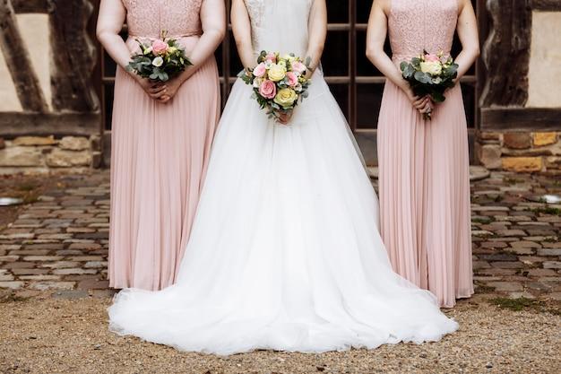 La novia y las damas de honor en un elegante vestido están de pie y sosteniendo ramos de flores en colores pastel.