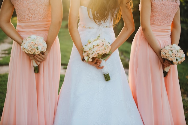 La novia y las damas de honor en un vestido elegante están de pie y sosteniendo un ramo de mano.
