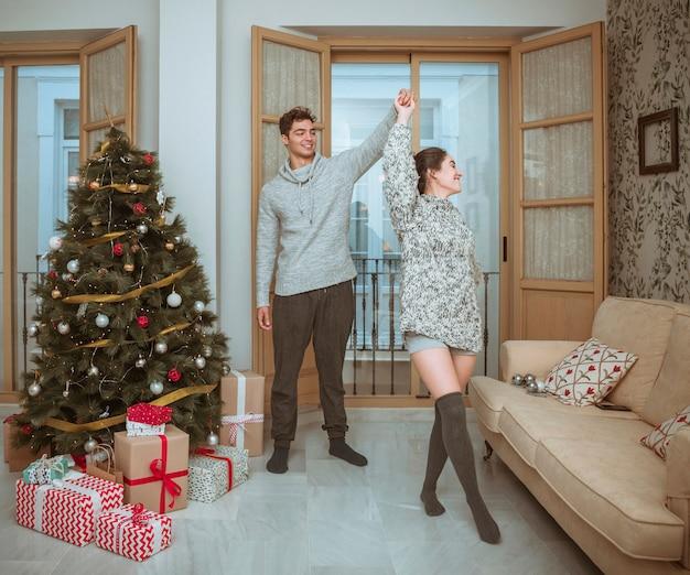 Novia dando vueltas bailando con su novio cerca del árbol de navidad