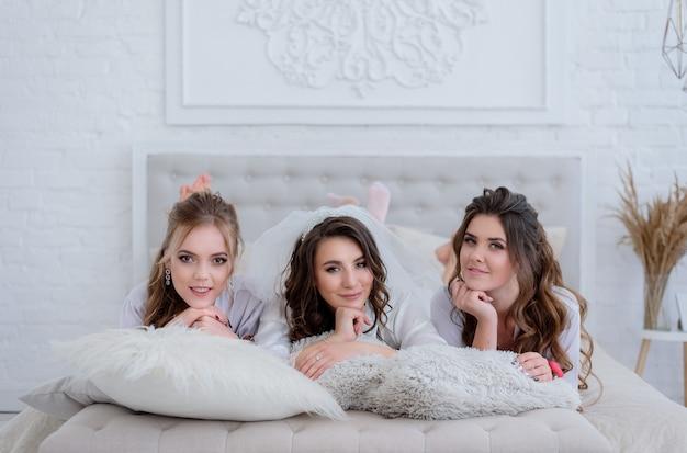 La novia y dos damas de honor atractivas yacen en la cama blanca en la habitación blanca de lujo