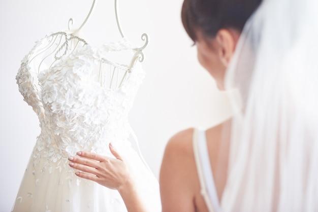 La novia elegante pone un vestido de novia en su habitación.