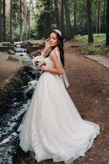 Una novia elegante con un vestido blanco y guantes sosteniendo un ramo se encuentra junto a un arroyo en el bosque, disfrutando de la naturaleza.una modelo con un vestido de novia y guantes en un parque natural.belarús.