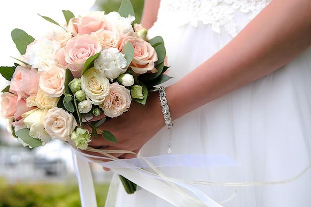 La novia en un elegante vestido de novia blanco está sosteniendo un hermoso ramo de diferentes flores y hojas verdes. tema de la boda