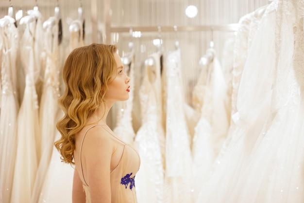 La novia elige un vestido de novia en la tienda.