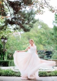 Novia encantadora en un vestido de melocotón gira antes de fuente en el jardín