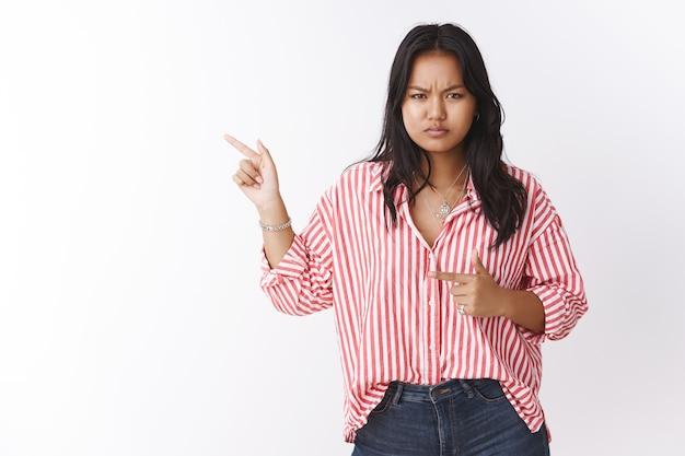 Novia enojada y disgustada que hace preguntas sobre la chica en la casa del novio, apuntando hacia la izquierda insatisfecha e irritada, frunciendo el ceño y entrecerrando los ojos molestos, posando frustrada sobre una pared blanca