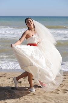 Novia feliz caminando por una playa de mar, día soleado