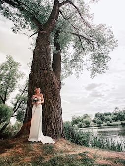 Novia feliz de pie junto a un gran árbol viejo.
