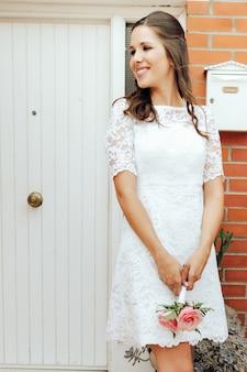 Novia feliz que sostiene su pequeño ramo de la boda de rosas rosadas en la puerta blanca. concepto del día de la boda
