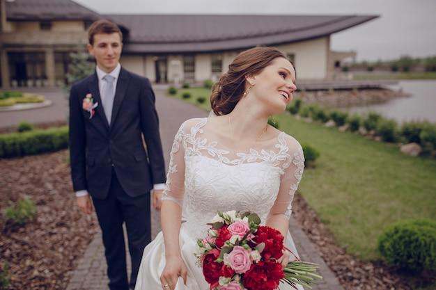 Novia feliz sujetando el ramo con su marido detrás