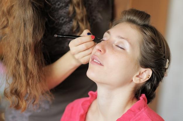 Novia hermosa joven que aplica maquillaje de la boda del artista de maquillaje profesional