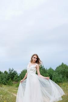 Novia hermosa joven en vestido de novia elegante blanco al aire libre, maquillaje y peinado