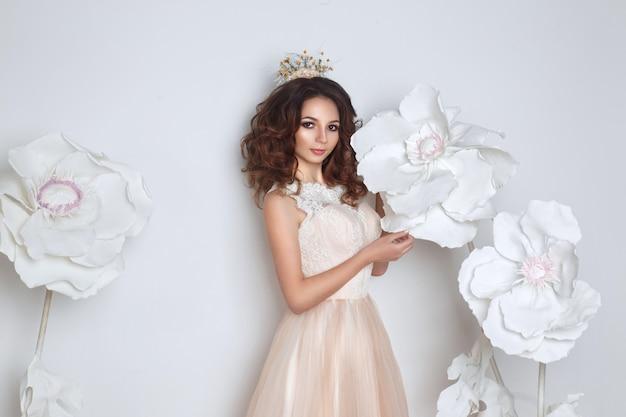 Novia hermosa que presenta en vestido de boda del melocotón y corona de la flor en un blanco. gran decoración de flores blancas