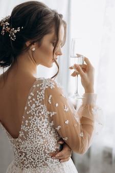 Novia hermosa que sostiene el vidrio de champán