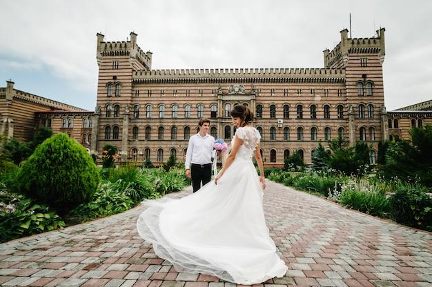 La novia hermosa del retrato está bailando para el novio y girando hacia atrás cerca de la arquitectura restaurada antigua, edificio antiguo, casa vieja afuera, palacio vintage al aire libre.