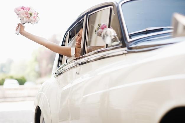 La novia hermosa se sienta con el ramo de la boda en un coche retro y se divierte