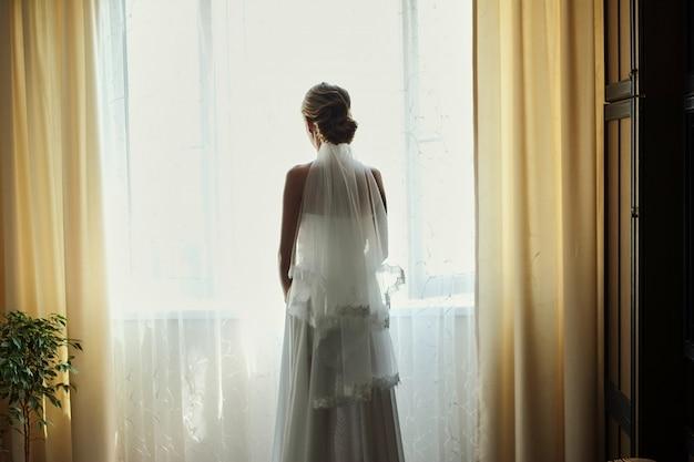 Novia hermosa en el vestido de boda blanco que coloca su dormitorio y que mira en ventana