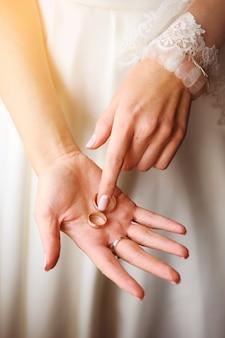 Novia hermosa en un vestido de boda que se sostiene en la palma del anillo, primer.