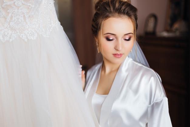 Novia con hermoso maquillaje en bata de baño blanca. primer plano de la novia