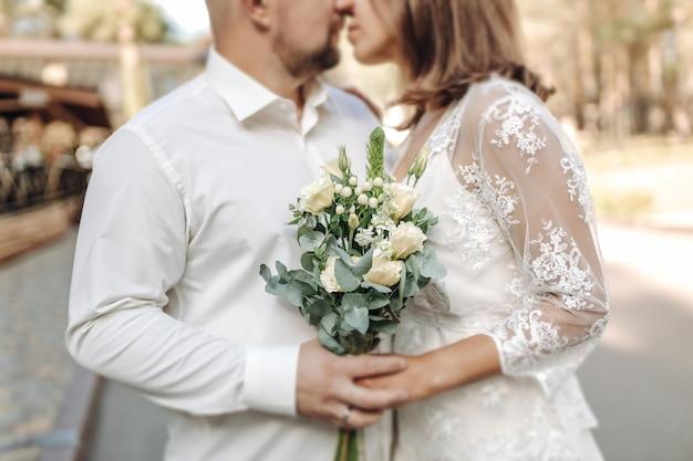 Una novia con un hermoso vestido con una cola sosteniendo un ramo de flores y vegetación.