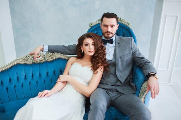Novia en hermoso vestido y novio en traje gris sentado en el sofá en el interior