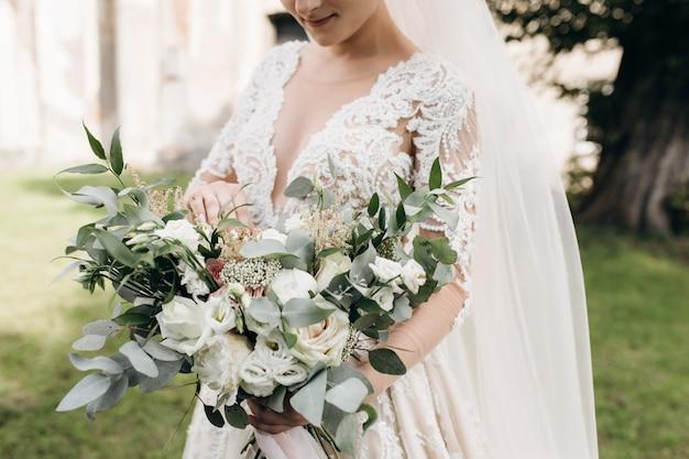 La novia en el hermoso vestido sostiene un ramo de novia con ramas de decoración verde y rosas blancas
