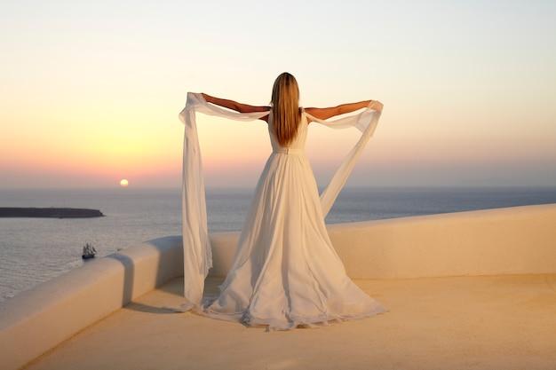 Novia en la isla de santorini. atardecer crepúsculo.