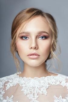 Novia joven en un lujoso vestido de novia blanco