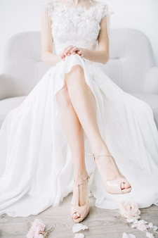 Novia joven sentada en el sofá con las piernas desnudas en zapatos de tacón de color rosa y pétalos de flores de color rosa. concepto de moda de boda festiva.